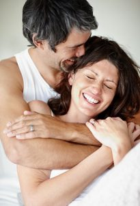 Portrait of mature couple enjoying themselves - Man embraces woman from back
