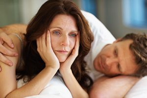 Sexual related problems - Middle aged woman lying on bed beside her husband in deep thought